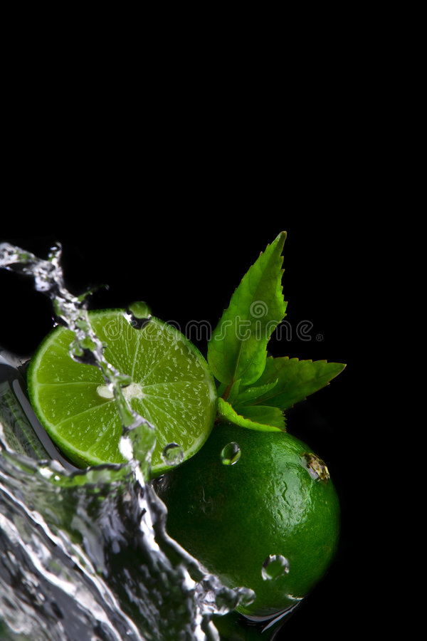 Splashed limes. Close up view of fresh limes getting splashed by water stock image
