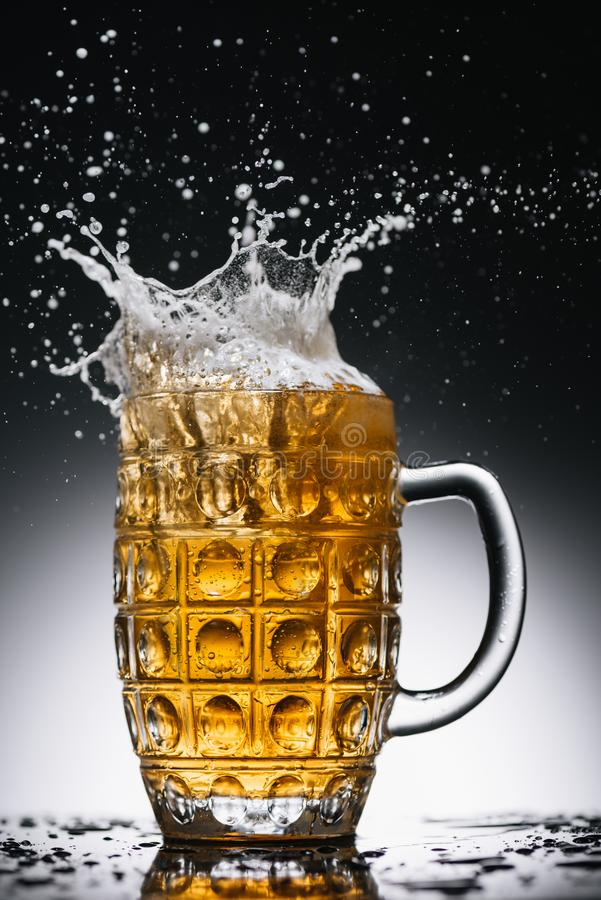 Splashes of cold light alcohol beer in mug stock photo