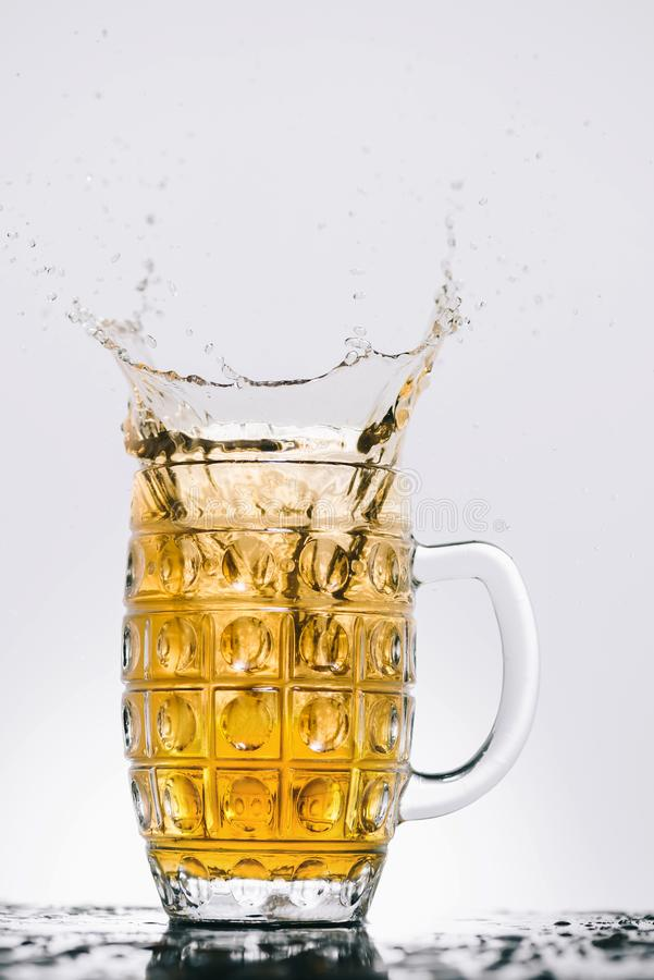Splashes of cold light beer. In transparent glass royalty free stock images