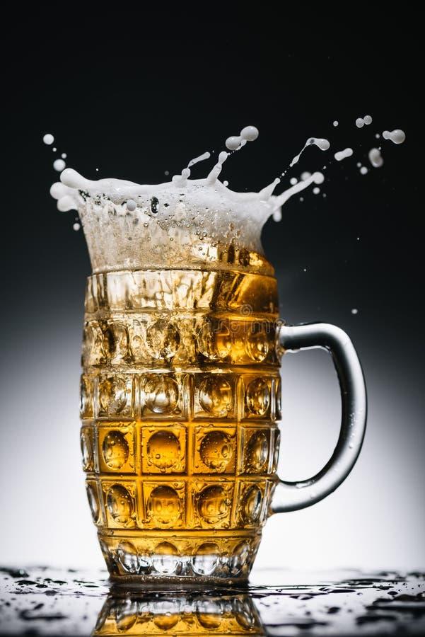 Splashes of fresh light beer in glass on black. And white stock image