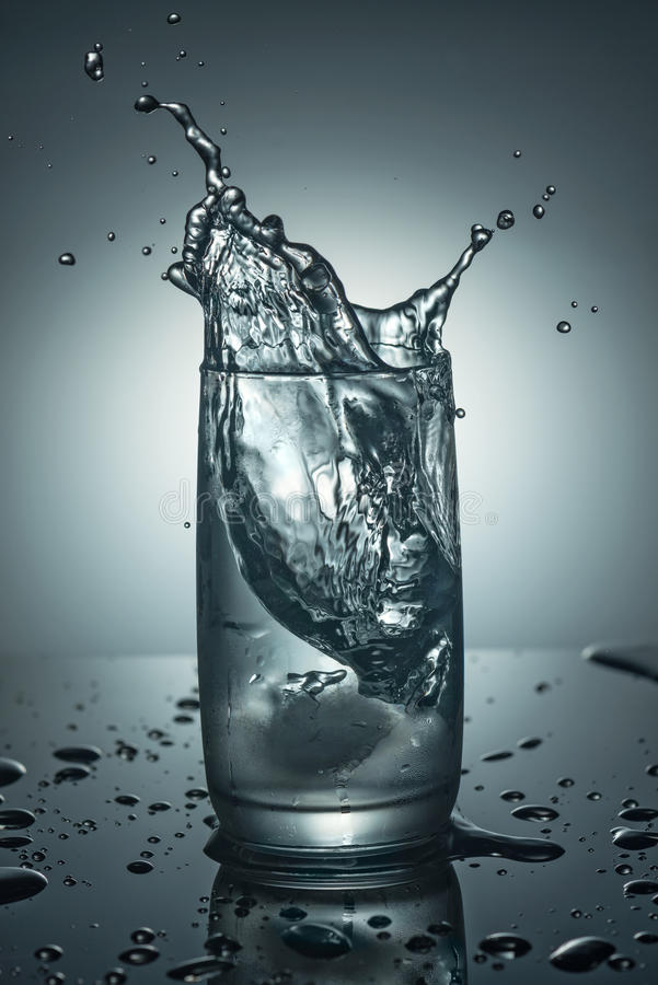 Splashes in a glass of pure cold water. With an ice cube stock image
