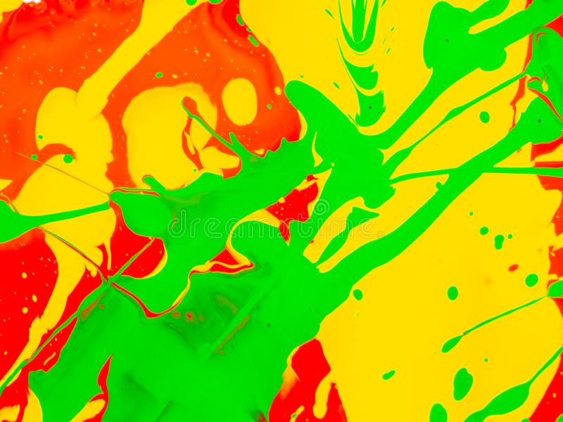 Splashes of red and yellow green paint on a white background stock images