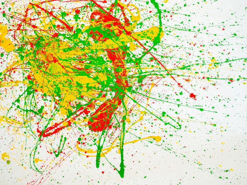 Splashes of red and yellow green paint on a white background stock image