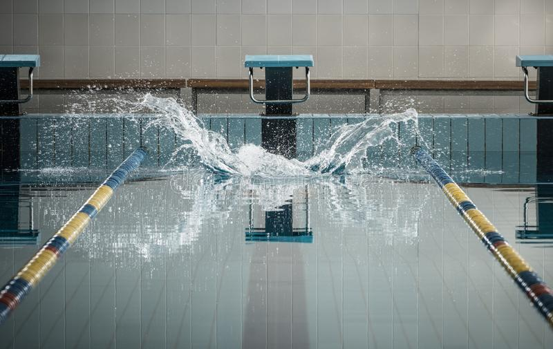 Splashes after swimmers jump. In a swimming pool stock image