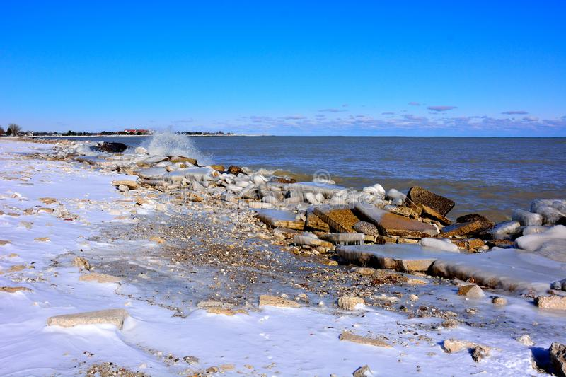 Ice coated shoreline in autumn at Lake Michigan. Splashing and crashing large waves and spray in November during an unusual cold snap create beautiful ice stock photos