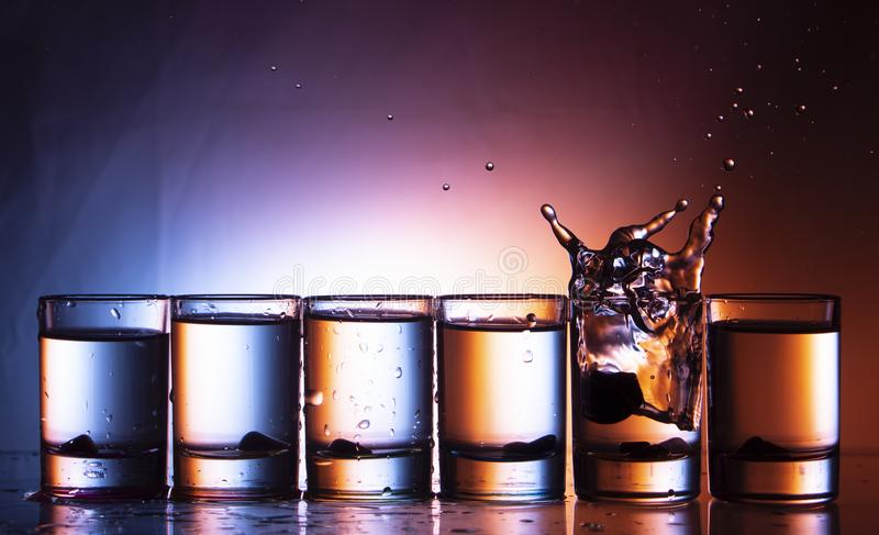 splashing fluid in a glass. That row of glasses on a blue-red background stock image
