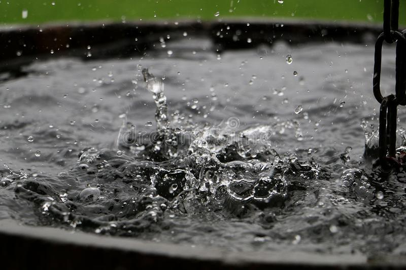 Splashing rain in a barrel. Rain is falling in a wooden barrel full of water in the garden royalty free stock photography