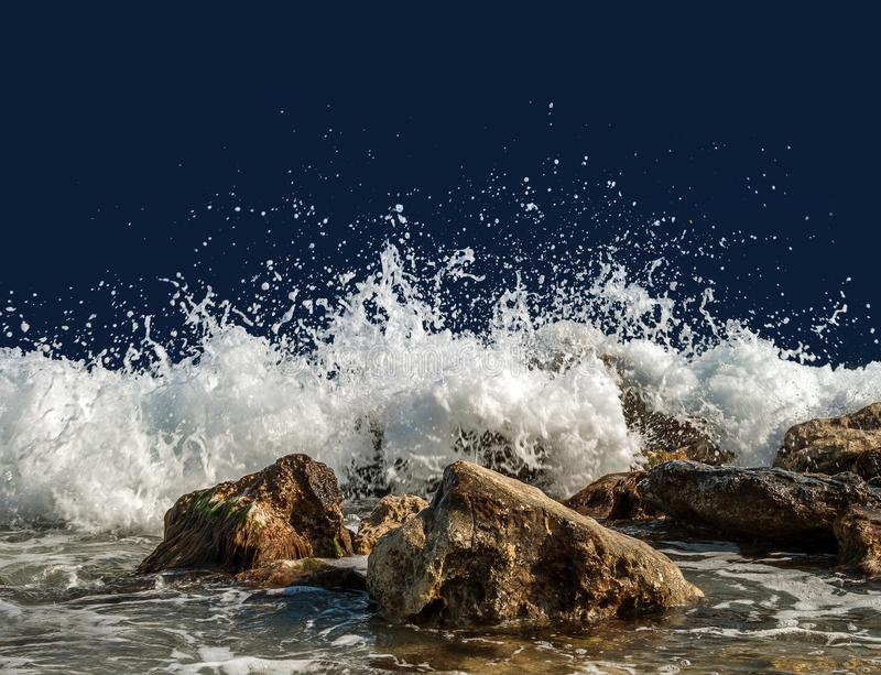 Splashing sea water on rocks isolated on a dark background stock image