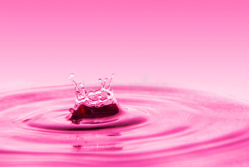Splashing water drops. On a pink background, for backgrounds or initial submissions royalty free stock images