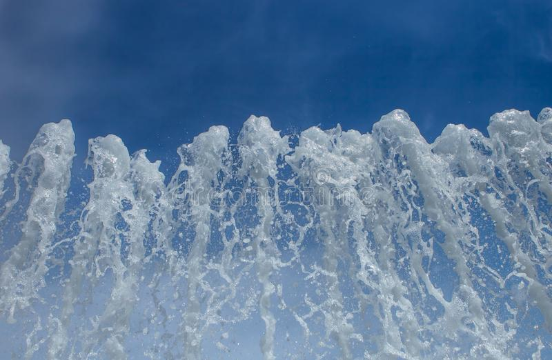 Splashing water of a fountain on blue sky background stock photos