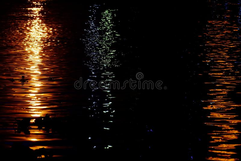 Blurred colorful lights reflection on water surface with river waves and dark background royalty free stock photo