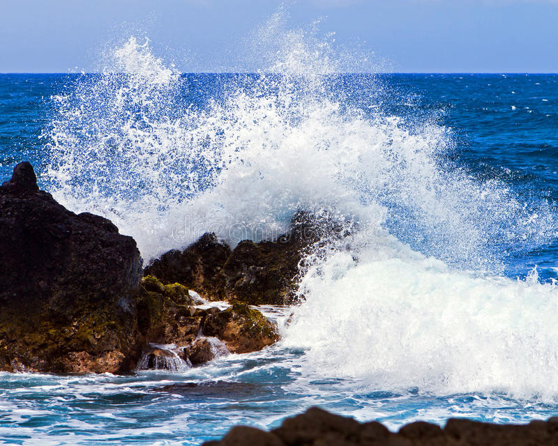 Splashing wave. The relentless play of waves breaking over lava rock on Maui's remote shoreline near Hana stock photo