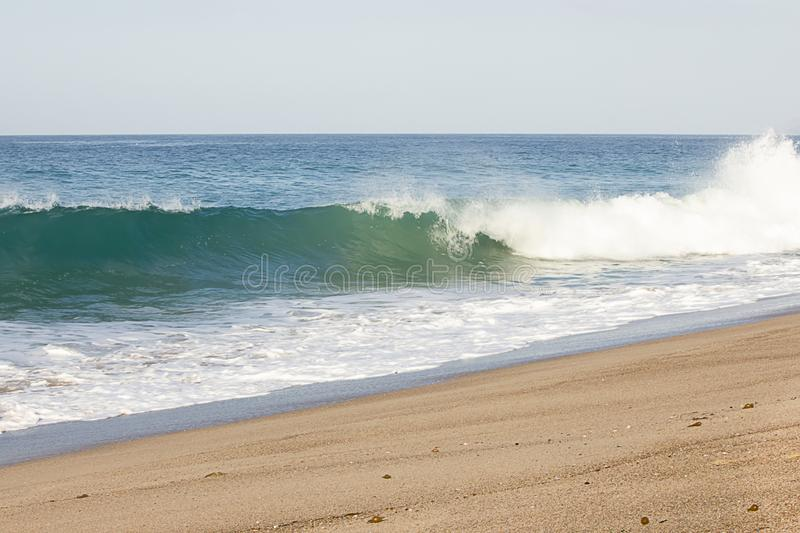 Splashing wave breaking from swelling wave in froth of backwash on sandy beach. On sunny morning stock photography