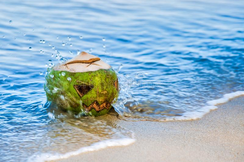 A splashing wave crashes into a pumpkin-shaped coconut for Halloween. young green coconut in ocean water with a scary face carved royalty free stock image