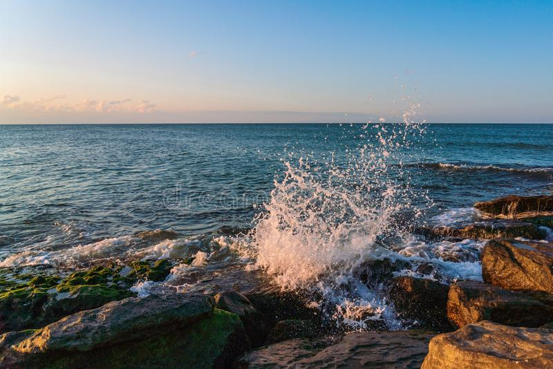 Splashing waves on the coastal cliffs at sunset. Time stock images