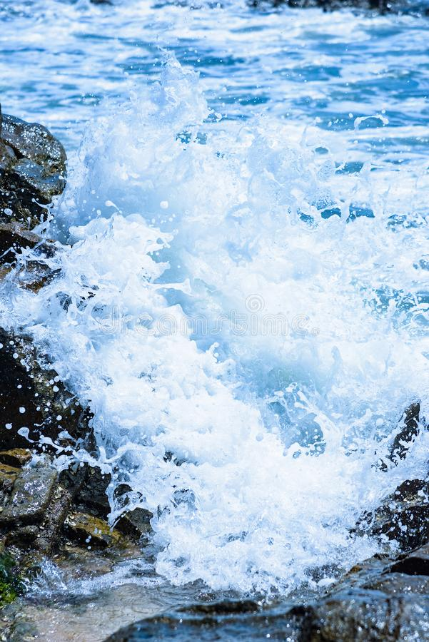 Splashing waves crashing on the rocky shore at dawn sun royalty free stock photography