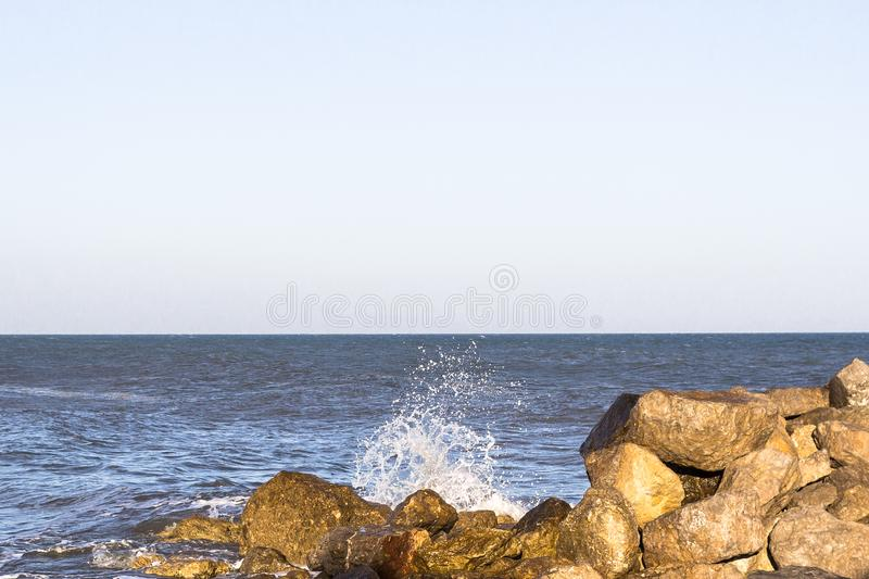 Splashing waves in the sun. Tidal bore. Sea in the sunset. Splashing waves in the ocean. The waves beat against the stones. A mound of cobblestones. Breakwater royalty free stock photo