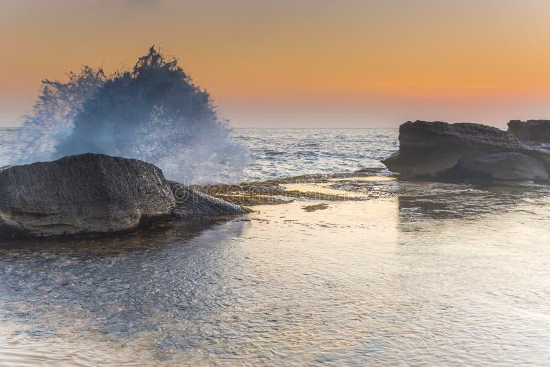 Splashy Zeegezicht met Rotsen in Zachte Sinaasappel royalty-vrije stock fotografie