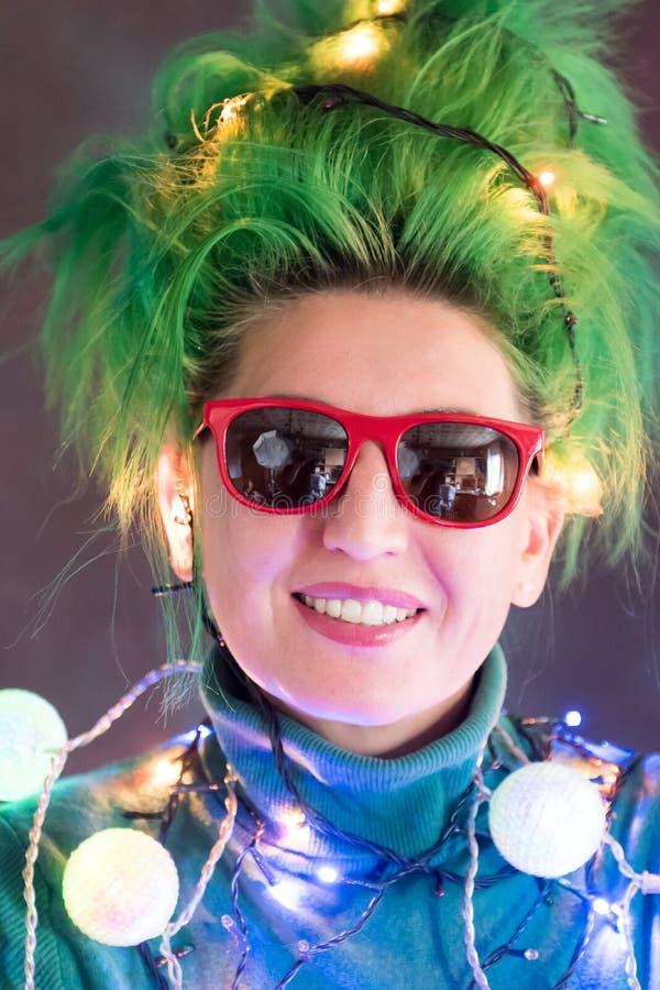 Splended flicka med iklädda julgirlander för grönt hår En flicka visar en julgran Begreppet av ett bra lynne på a arkivbild