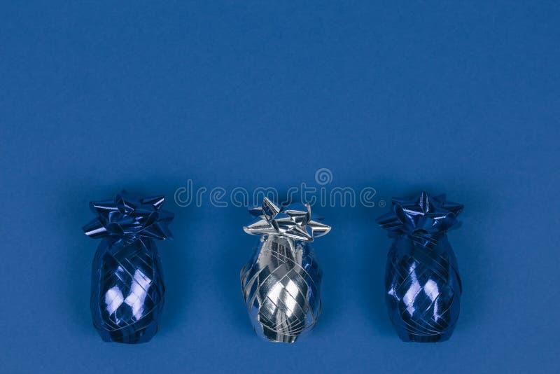 Splendendo l'ornamento blu e d'argento di Natale allineato sul fondo blu immagini stock libere da diritti