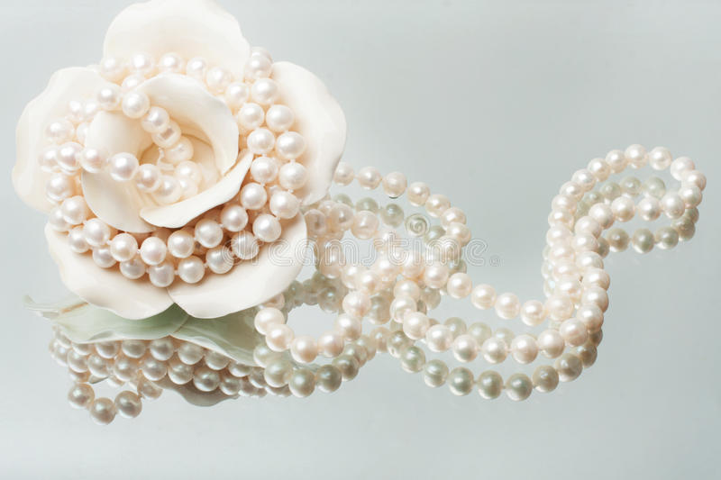 Splendid necklace of white pearls. With a porcelain vase stock images