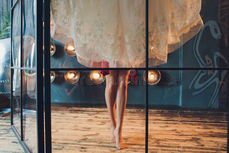 Splendida, la sposa in vestito di lusso bianco sta preparandosi per nozze Preparazioni di mattina Donna che mette sul vestito fotografie stock