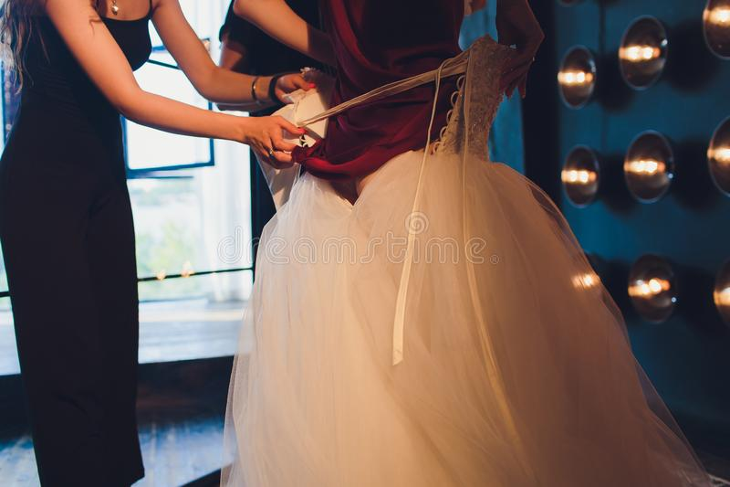Splendida, la sposa in vestito di lusso bianco sta preparandosi per nozze Preparazioni di mattina Donna che mette sul vestito immagine stock libera da diritti
