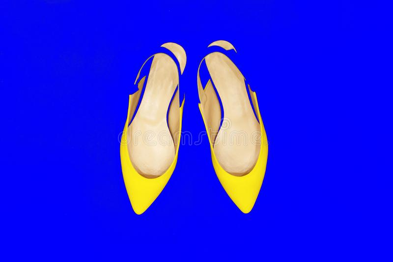 Splendor mody żółci buty na błękitnym neonowym tle minimalizm Jaskrawej sztuki Kolorowy styl Luksusowa B?yszcz?ca Partyjna dama M obraz royalty free