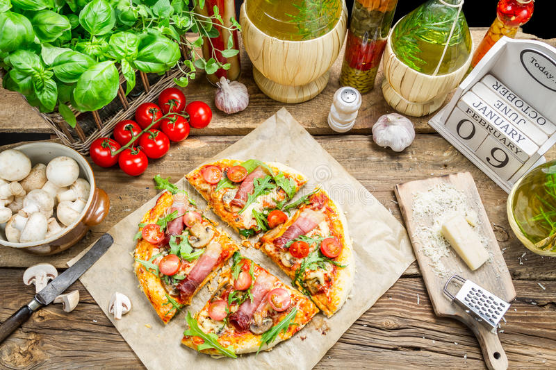 Split baked pizza with fresh vegetables stock photography