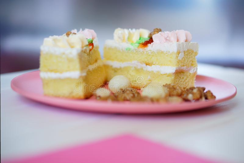 Split biscuit cake with protein cream and nuts in a plate on a white, pink and silver background. Shallow depth of field stock image