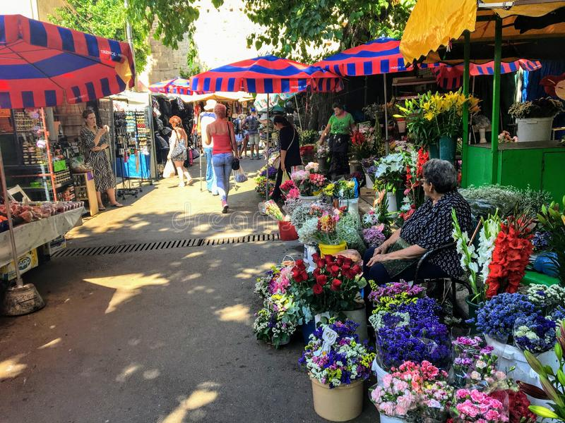 A weekend market during the summer in Split, Croatia.  A local elderly woman is selling an array of colourful flowers. Split, Croatia - July 6th, 2019: A royalty free stock images