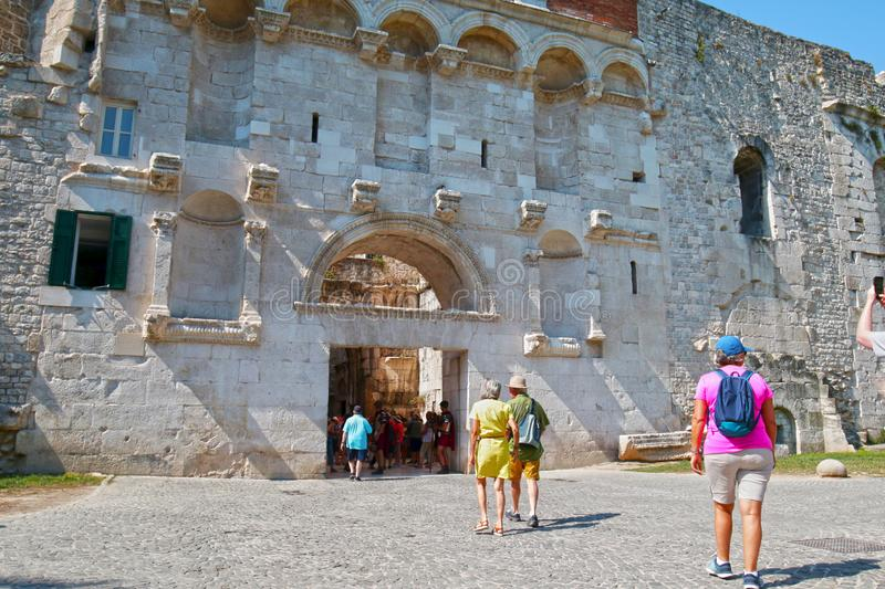Split / Croatia - June 26, 2019: Tourists entering ancient Golden Gate to the Diocletians Palace section of Old Town Split, Croati royalty free stock photography