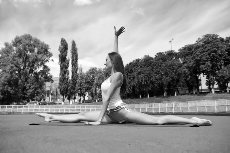Split is easy for her. Stretching muscles every time training. Coach tips and advice. Woman flexible body practice split. On fitness mat outdoors nature royalty free stock image