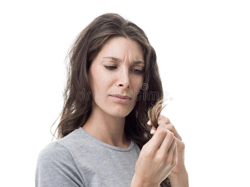Split ends and damaged hair. Upset angry woman checking split ends on her damaged messy hair, hair care concept royalty free stock photo