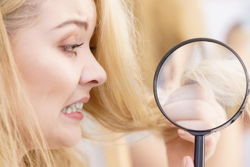 Woman magnifying her split ends hair stock photos