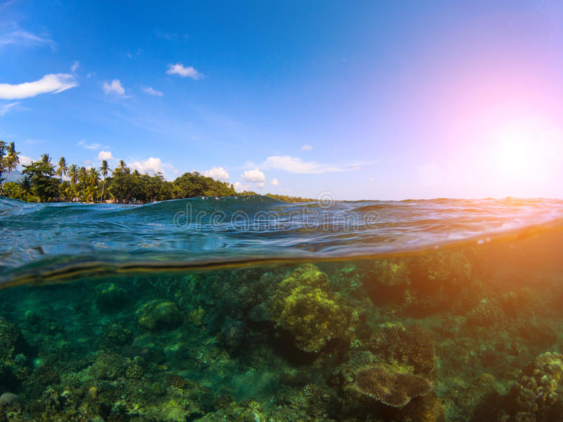 Split landscape with sea and sky. Double photo with tropical island and underwater coral reef. Above and below sea waterline. Exotic seashore panorama. Split stock photography