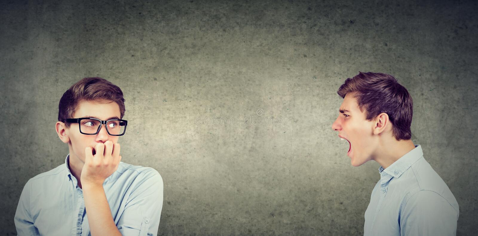 Split personality. Angry young man screaming at scared anxious himself royalty free stock image