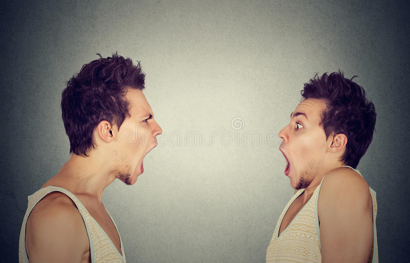 Split personality. Angry young man screaming at scared himself royalty free stock image