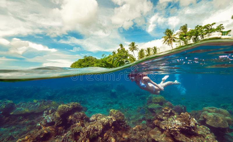 Split underwater photo of a girl snorkeling with mask in tropical ocean enjoying summer vacation on exotic island. Beautiful Coral reef and a woman floating in royalty free stock photography