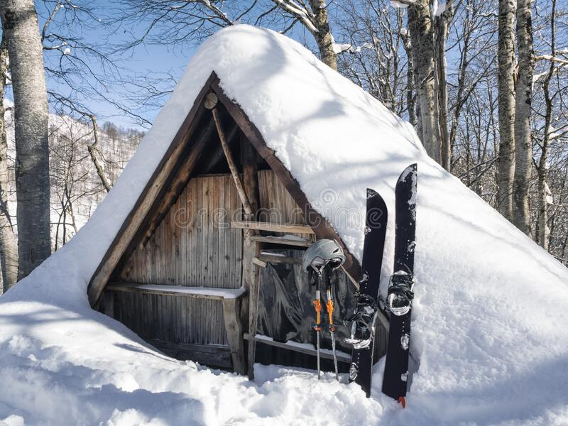 Splitboard and poles in snow at wooden house of shepherds shed background. Sport equipment for ski touring stock images