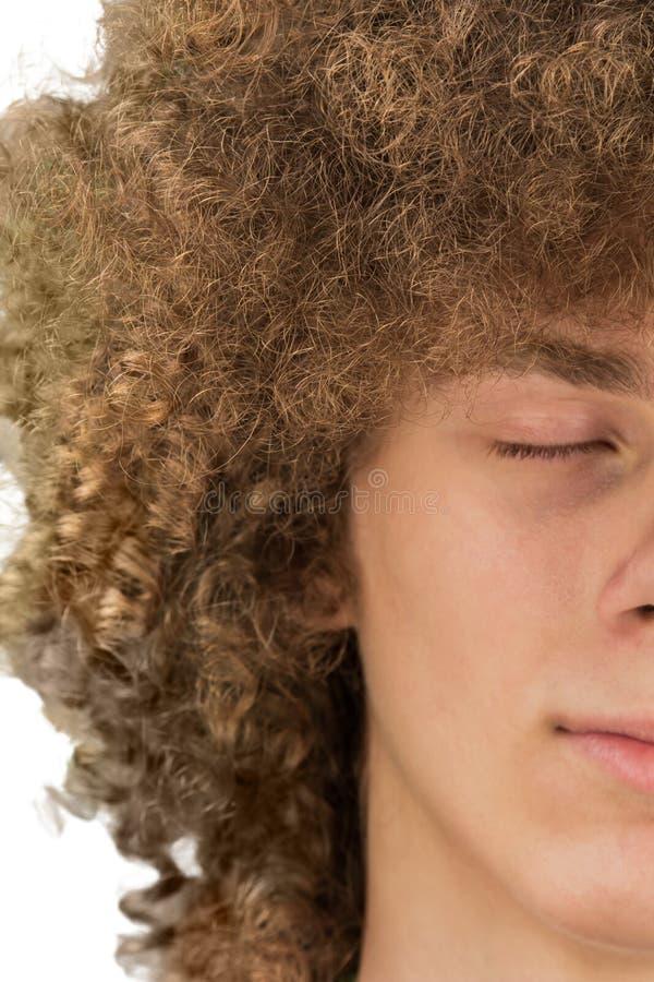 Splited в половинном подрезанном портрете молодого курчавого европейского человека с длинным вьющиеся волосы и закрытые глаза зак стоковая фотография rf