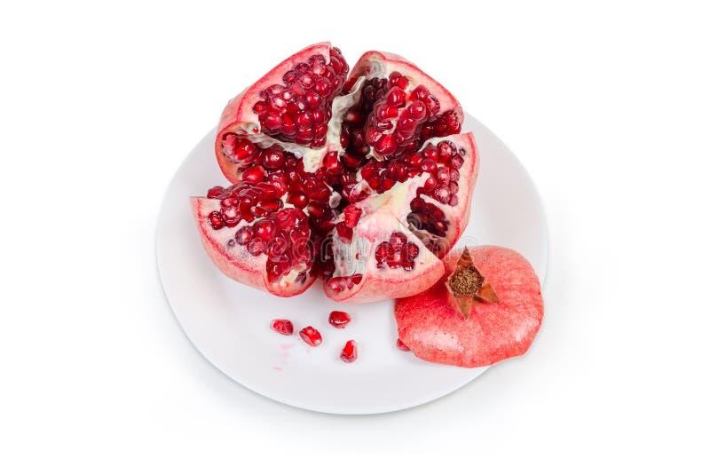 Splitted granatäpplefrukt på den vita maträtten på vit backgroun royaltyfri foto