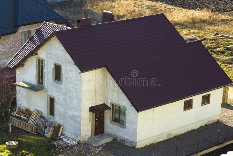 Splitterny rymlig tegelsten rappade det bostads- familjhuset för två berättelse med det bruna belägga med tegel taket och fönster royaltyfri bild