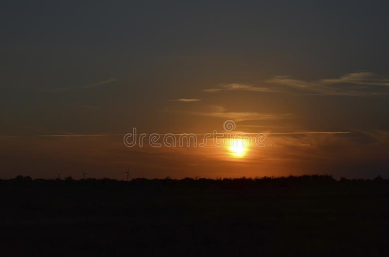 Splitting the sky with a strip of clouds during the summer sunset stock image