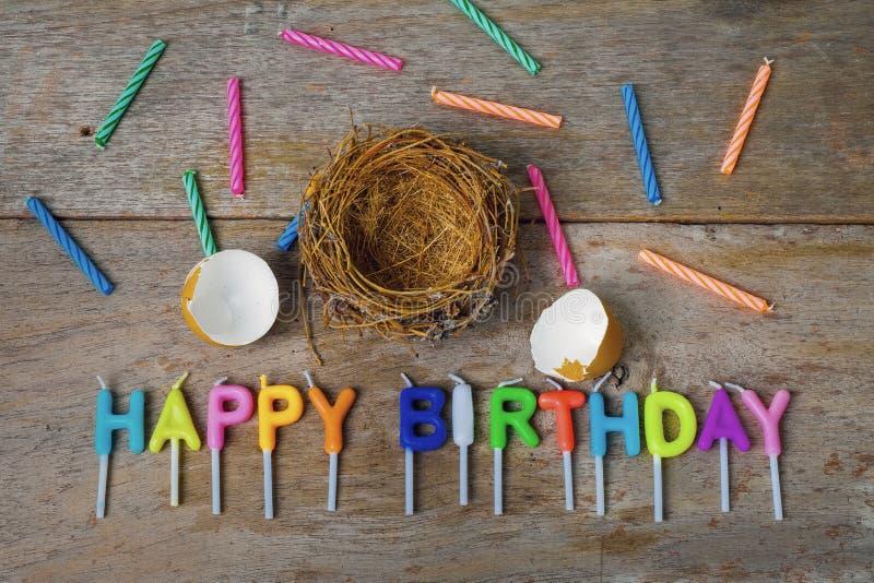 Splittrad äggskal med redet och stearinljus för den lyckliga födelsedagen Conce arkivfoton