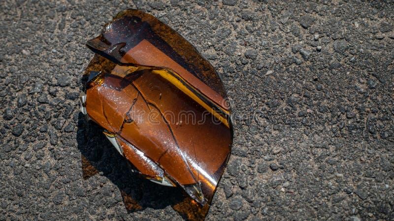 Splittrad ölflaska på jordningen royaltyfri fotografi