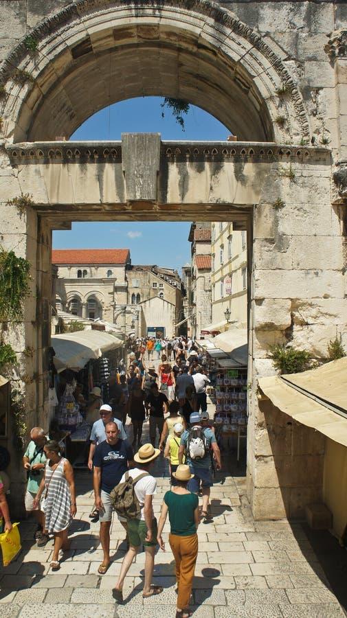 Splittring Kroatien - 07/22/2015 - folk som går till och med den östliga silverporten, del av den Diocletian slotten, solig dag,  royaltyfria foton