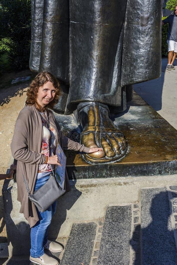 SPLITTRING KROATIEN, OKTOBER 01, 2017: Turist som går och trycker på Gregoryen om Nin fot för lycka och hälsa i splittring arkivbilder