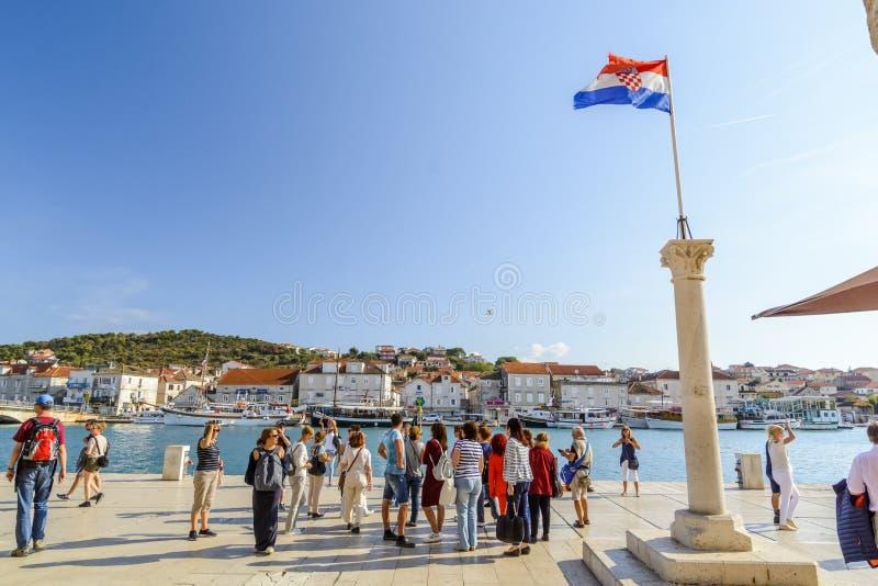 SPLITTRING KROATIEN, OKTOBER 01, 2017: turist som går på stranden och tar bilden av den kluvna marina nära den kroatiska flaggan arkivfoto
