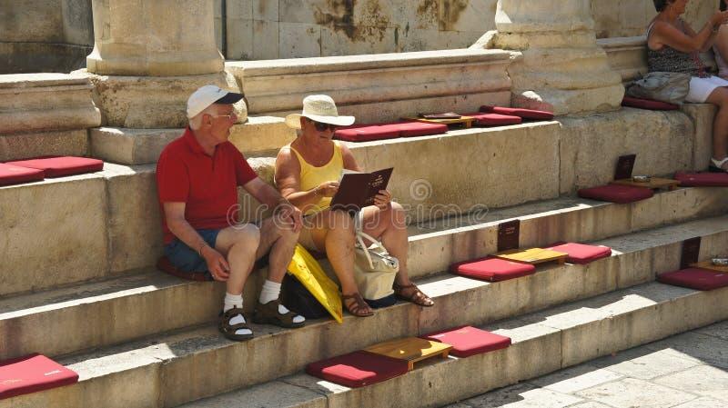 Splittring Kroatien - 07/22/2015 - turistläsningmeny på trappan av den Diocletian slotten, solig dag, Dalmatia arkivfoto